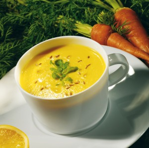 Carrot soup with cumin seeds and reduced orange juice rocket leaves