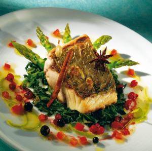 Pan-fried sea bass with mild spices, salad of warm spinach, asparagus and berries